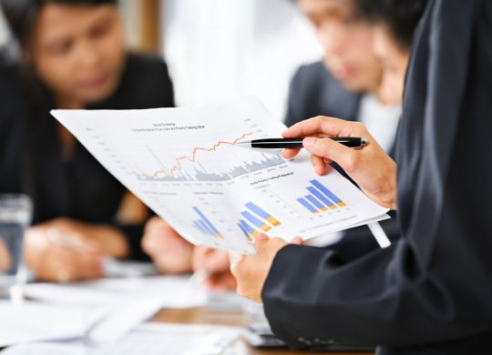 Businesswoman examining graphs with other working people on background
